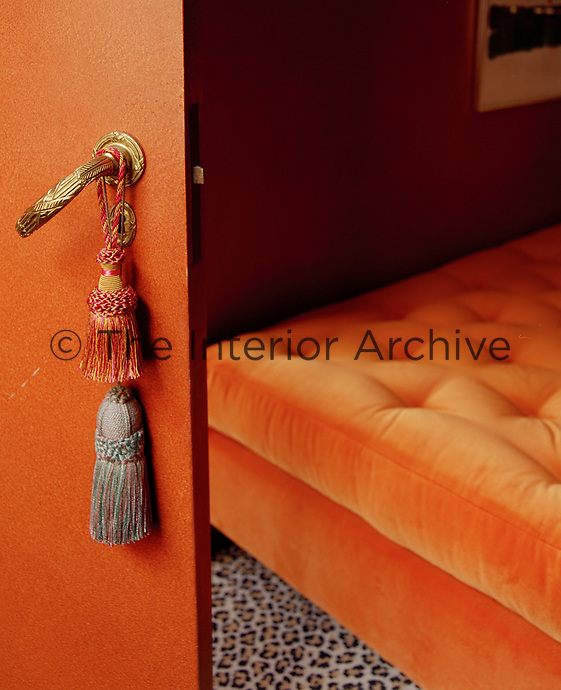 A glimpse through an open door of a bright orange velvet Chesterfield daybed on a daring leopard print carpet
