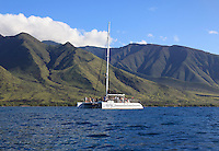 Boat with tourists at Olowalu, Maui, Hawaii  with the West Maui Mountains behind.