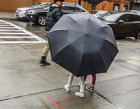 Two children walking under huge umbrella.