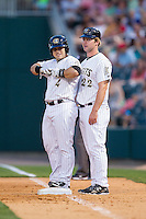 Charlotte Knights first base coach Matt Davidson (22) chats with Josh Phegley (4) during the game against the Lehigh Valley IronPigs at BB&T Ballpark on May 8, 2014 in Charlotte, North Carolina.  The IronPigs defeated the Knights 8-6.  (Brian Westerholt/Four Seam Images)