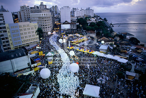 Salvador, Brazil. Filhos de Gandhi carnival procession snaking white through the crowds seen from above. Bahia State.