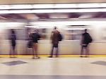 People standing on a subway platform waiting for the arriving train. Artistic motion blur. TTC, Toronto, Ontario, Canada.