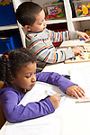 Education preschool 3-4 year olds boy and girl sitting near each other at table girl tracing her name with dry erase marker, boy playing with wooden peg puzzle