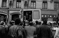 Carrefour boulevard Lazare-Carnot et allées François-Verdier. 6 février 1978. Scène de manifestation : au 1er plan groupe de manifestants discutant avec des policiers (plan taille de dos) ; au 2nd plan un homme est dans la cabine d'un camion, portière ouverte, parle à un policier ; en arrière-plan façade immeuble. Cliché pris lors d'une manifestation organisée par une trentaine de transporteurs et artisans locaux pour protester contre le chantier de l'autoroute A61 donné à une grosse société du centre de la France. Manifestation patronée par la Confédération Intersyndicale de Défense et d'Union Nationale des Travailleurs Indépendants (CIDUNATI).