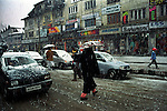 A woman crosses a road at Lal Chowk in Srinagar during a snowfall. Daily life coming to a easy flow after the decission of seize fire taken by the neighbouring countries of India and Pakistan, Kashmir valley, India