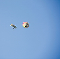 A parachutist begins his descent having leapt from a hot air balloon.