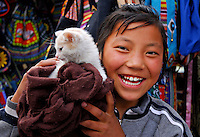 Tibetan girl with kitten at a market stall, Barkhor Square, Lhasa, Tibet.