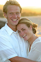 Couple wearing white smile and hug. Golden evening light on the ocean and mountains in the background.