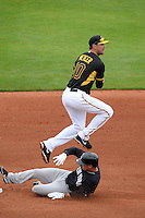 Shortstop Jordy Mercer (10) of the Pittsburgh Pirates turns a double play as Dean Anna (93) slides in during a spring training game against the New York Yankees on February 26, 2014 at McKechnie Field in Bradenton, Florida.  Pittsburgh defeated New York 6-5.  (Mike Janes/Four Seam Images)