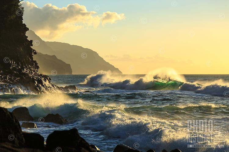 Waves break in the light of the setting sun at Ke'e Beach, Ha'ena State Park, Na Pali Coast, Kaua'i.