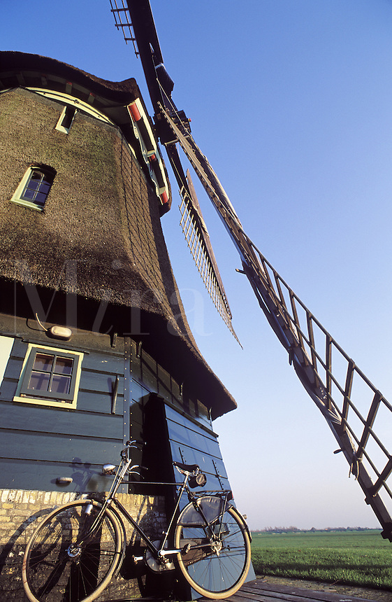 Holland, bicycle leaning against a traditional Dutch windmill