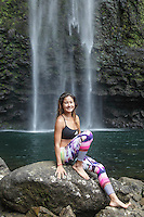A young woman who hiked a side trail from Kalalau Trail to Hanakapi'ai Falls rests on a nearby rock, Kaua'i.