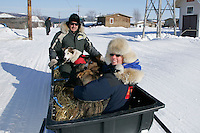 """Monday March 12, 2007   ----   Iditarod air force pilot Danny Davidson and """"Teacher on the Trail"""" Kim Slade sit with 5 dropped dogs in a sled being towed to the airport at Kaltag."""