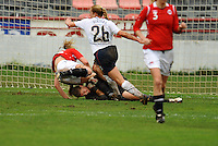 USA goalkeeper Nicole Barnhart covers up the ball as an oncoming Norwegian attacks.  The USA defeated Norway 2-1 at Olhao Stadium on February 26, 2010 at the Algarve Cup.
