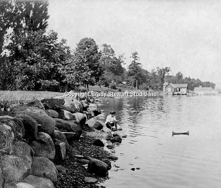 Lakewood NY: Young boy kneeling on the shore and playing with his toy canoe on Lake Chautauqua. Photographs taken during a church field trip to Chautauqua Institution in New York (Lake Chautauqua). The Stewart family and friends visited Chautauqua during 1901 to hear Stewart relative, Dr. S.H. Clark  speak at the institute. Alice Brady Stewart chaperoned and Brady Stewart came along to photograph the trip.  The Gallery provides a glimpse of how the privileged and church faithful spent summers at Lake Chautauqua at the turn of the century.