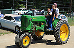 Boys riding farm tractor at Cheshire Fair in Swanzey, New Hampshire USA