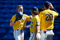Michigan Wolverines left fielder Miles Lewis (3) is congratulated by teammates after hitting a home run during a game against Army West Point on February 17, 2018 at Tradition Field in St. Lucie, Florida.  Army defeated Michigan 4-3.  (Mike Janes/Four Seam Images)