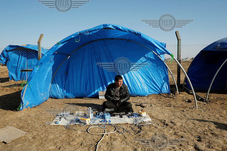 An IDP man who has a business charging phones and batteries for 250 Iraqi Dinars at the Jada'ah refugee camp.