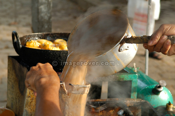 India, Kerala, Fort Cochin (Cochi, Kochi). Tea and streetfood (pakora, fritters) being prepared in a small mobile cook-shop.  No releases available.