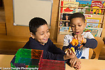 Education Preschool 4 year olds two boys playing together with plastic animal and human figure after constructing building with magnetic blocks