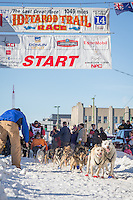 Danny Seavey and team leave the ceremonial start line at 4th Avenue and D street in downtown Anchorage during the 2014 Iditarod race.<br /> Photo by Jim R. Kohl/IditarodPhotos.com