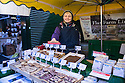 London, UK. 15.11.2014. Female stallholder offers a sample of a 'Flaxjack' (flapjack made with linseed meal) at Borough Market. Photograph © Jane Hobson.