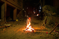 Nepali people who lost their home in earthquake warm themselves next to a campfire at night in Bhaktapur, near Kathmandu, Nepal. May 04, 2015