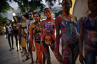 Art students covered with body paint stand in a row, including a girl with revolutionary figures Che Guevara and Camilo Cienfuegos pianted on her torso and crotch in Guantanamo, Cuba on 20 February 2007.