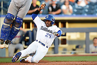 Tulsa Drillers outfielder Delta Cleary Jr. (24) slides home safely during a game against the Midland RockHounds on May 31, 2014 at ONEOK Field in Tulsa, Oklahoma.  Tulsa defeated Midland 5-3.  (Mike Janes/Four Seam Images)