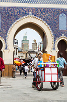Fes, Morocco. Ice Cream Cone Vendor Leaving Fes El-Bali (Old City) through the  Bab Boujeloud.  The minaret of the Bou Inania medersa is in the background.