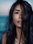 Sensual beauty portrait of a young asian woman with long wet dark hair full of sand particles covering her face with beautiful exotic features Image © MaximImages, License at https://www.maximimages.com