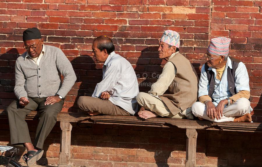 Nepal, Patan.  Four Nepali Men Sitting on Bench in Durbar Square.