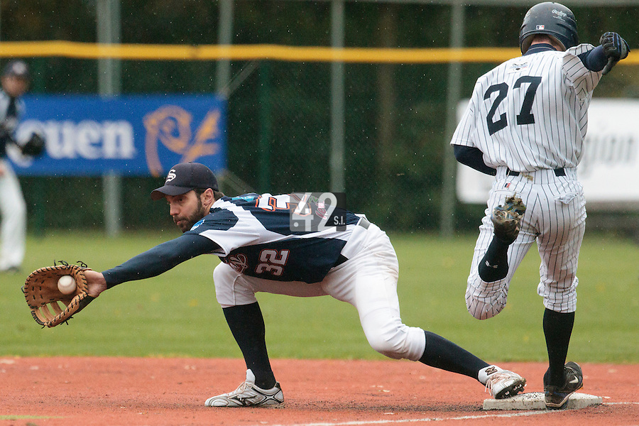 23 October 2010: Sebastien Boyer of Savigny catches the ball as Joris Bert reaches first base during Savigny 8-7 win (in 12 innings) over Rouen, during game 3 of the French championship finals, in Rouen, France.