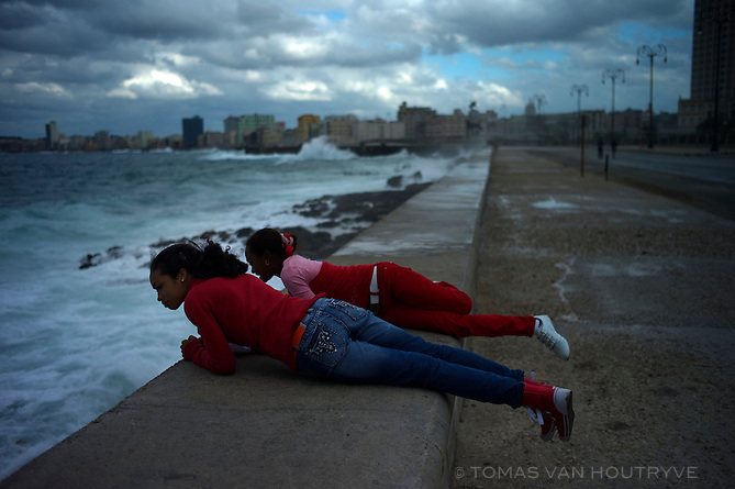 Girls look into the ocean perched on top of the wall of the Malecon  Havana, Cuba on Nov. 6, 2010. The Malecon seaside drive was closed to traffic due to large waves from tropical storm Tomas.
