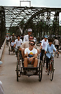 Danang, February 1988. Crossing the Perfume River and old French built bridge link the two sides of the city. There is an endless traffic on that bridge. In a rickshaw Roger Cote, a US Veteran having a good time.
