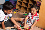 Education preschool 3 year olds two boys playing with each other and train set