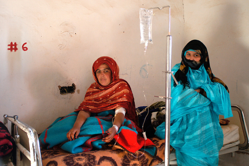 Two women wait in a hospital on December 13, 2003. Saharawi people have been living at the refugee camps of the Algerian desert named Hamada, or desert of the deserts, for more than 30 years now. Saharawi people have suffered the consecuences of European colonialism and the war against occupation by Moroccan forces. Polisario and Moroccan Army are in conflict since 1975 when Hassan II, Moroccan King in 1975, sent more than 250.000 civilians and soldiers to colonize the Western Sahara when Spain left the country. Since 1991 they are in a peace process without any outcome so far. (Ander Gillenea / Bostok Photo)