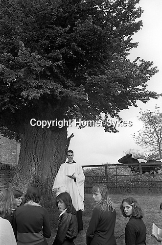 The Wicken Love Feast, takes place on Ascension Day and celebrates the joining together of two parishes in 1587. Wicken Northamptonshire 1970s Uk.  Open air service under the Gospel Oak (Not sure here it may be an Elm) <br /> <br /> The Revd Peter Townsend of St John the Evangelist Parish Church