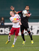 Raphael Augusto (12) of D.C. United fights for the ball with Dax McCarty (11) of New York Red Bulls during the game at RFK Stadium in Washington, DC.  New York Red Bulls defeated D.C. United, 2-0.