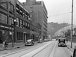 "Pittsburgh PA:  View looking west on Penn Avenue toward the Point Bridge.  Point Bride in the background along with the famous ""Drink Iron City"" sign."