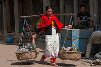 Bhaktapur, Nepal.  Newari Woman Carrying Baskets with aid of a Shoulder Pole (Nol).  Bhaktapur Women traditionally wear red and black.