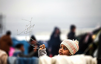 Pictured: A young girl plays with a piece of wire, possibly from the barbed-wire fence that now separates the two countries Monday 29 February 2016<br /> Re: A crowd of migrants has burst through a barbed-wire fence on the FYRO Macedonia-Greece border using a steel pole as a battering ram.<br /> TV footage showed migrants pushing against the fence at Idomeni, ripping away barbed wire, as FYRO Macedonian police let off tear gas to force them away.<br /> A section of fence was smashed open with the battering ram. It is not clear how many migrants got through.<br /> Many of those trying to reach northern Europe are Syrian and Iraqi refugees.<br /> About 6,500 people are stuck on the Greek side of the border, as FYRO Macedonia is letting very few in. Many have been camping in squalid conditions for a week or more, with little food or medical help.