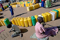Water queue at the Pabbo Internally Displaced PeopleÕs (IDP) camp. Clean water in the camp is now impossible to come by and must be boiled to rid it of waterborne disease. Pabbo is the largest IDP in Uganda, holding an estimated 63,000 people. The IDP camps of Northern Uganda formed when areas in the region became unsafe for civilians to live. Clean water, sanitation, food, employment, education, moral living, and human rights have almost been entirely depleted. Furthermore, congestion within the camps has contributed to major health and living problems. With 1.6 Ð 2 million people displaced and with an almost total lack of resources to care for them, the local peopleÕs very existence physically, emotionally and culturally is at stake. The war between the LordÕs Resistance Army and the Ugandan military has been transpiring since 1986. Thousands have been killed and abducted. Pabbo, Gulu District, Uganda, Africa. December 2005 © Stephen Blake Farrington