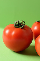 Fresh tomatoes on green background