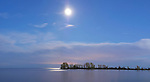Beautiful atmospheric panoramic view on lake Ontario after sunset with moonlight from a glowing moon in the sky reflecting in the water Toronto Ontario Canada
