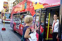 Milano City Sightseeing, servizio di tour turistici su autobus a due piani scoperti. Una guida turistica accoglie un passeggero --- Milan City Sightseeing, city tours service with open top double-decker buses. A tour guide welcomes a passenger