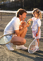 Father teaching daughter to play tennis