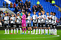 Swansea City players take part in a minutes applause during the Sky Bet Championship match between Cardiff City and Swansea City at the Cardiff City Stadium in Cardiff, Wales, UK. Sunday 12 January 2020