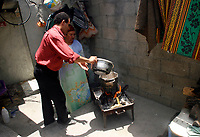 """Gaza.June.22.2008 Um suhil  cooked using wood fire with her sun, Um Suhail says: """"we got used to live among the graves of the dead. we are like them; depending on charities and handouts.""""""""The family was drove out from their original village in the 1948 when Jews forced thousands of Palestinians to migrate, establishing the State of Israe.June.22.2008l.""""photo by Fady Adwan/propaimages"""""""