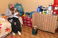 South Africa, Cape Town, Khayelitsha Township.  Mother Feeding Baby in her one-room Home, Cooking Apparatus on the Floor.
